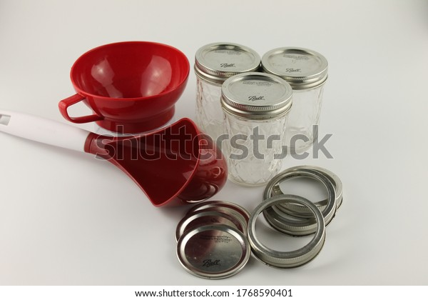 Upholland, Lancashire, UK, 03/07/2020: Canning supplies, ball mason jars, rings, lids, wide mouth funnel and large red ladle, isolated on white background