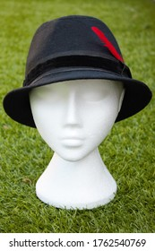 Upholland, Lancashire, UK, 24/06/2020, Black trilby hat with a red feather. Isolated on a white mannequin head, grass background, vertical format