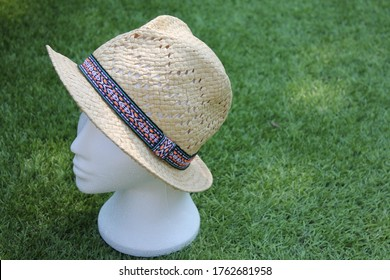 Upholland, Lancashire, UK, 24/06/2020, Straw trilby hat, on a white mannequin head, on a green blurred background in landscape, copy space to the right