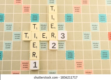 Upholland, Lancashire, UK, September 2020: Tier one, tier two and tier three on a scrabble board, local levels tighter restrictions and lockdown concept