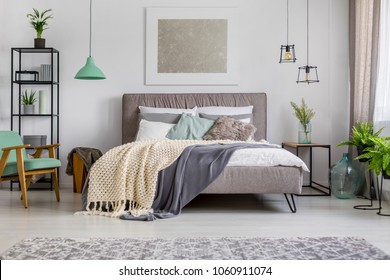 Upholstered double fabric bed with cozy blankets and pillows in a bright, modern interior with pastel furniture and decor