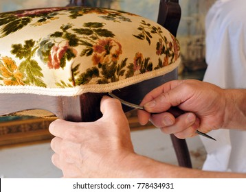 Upholsterer repairing the seat of a chair