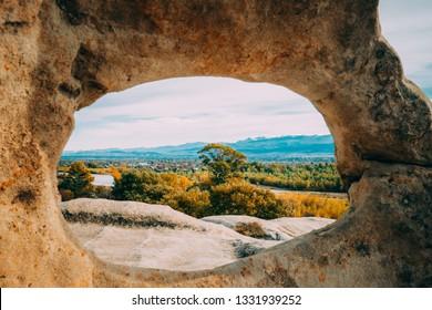 Uplistsikhe, Shida Kartli Region, Georgia. View Of Kvakhvreli Cityscape Through Natural Arch In Famous Landmark. Ancient Rock-hewn Town In Eastern Georgia. UNESCO World Heritage Site