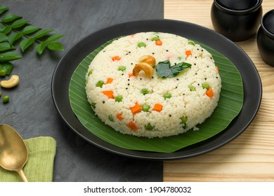 Upma made of samolina or rava upma, most famous south indian breakfast item which is arranged in a  black plate  and garnished with fried cashew nut and curry leaves with grey colour background.