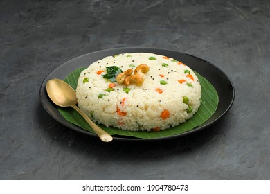 Upma made of samolina or rava upma, most famous south indian breakfast item arranged in a plate with banana leaf  and garnished with fried cashew nut and curry leaves with grey colour background.