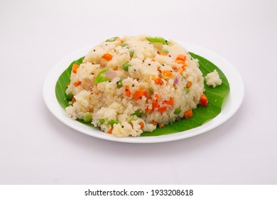 Upma made of samolina or rava upma, most famous south indian breakfast item which is  arranged in a  plate lined with fresh banana leaf placed on white textured background..