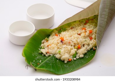 Upma made of samolina or rava upma, most famous south indian breakfast item which is beautifully arranged in a banana leaf  with empty small bowl nearby on white background.