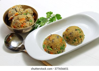 Upma, a south Inidan breakfast snack made of roated semolina, carrots and peas, selective focus.