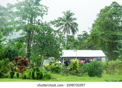 Upolu Island, Samoa - October 30, 2017: Samoan home with colorful laundry hanging outside the home, amongst green plants and trees in garden