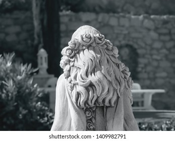 upper back view of a white stone female statue, curly long hair with a roses on her hair, black and white shot