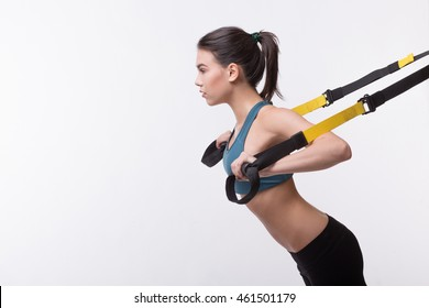 Upper body exercise concept. Beautiful woman exercising with suspension straps alone in studio. TRX concept isolated on white background.
