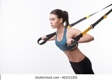 Upper body exercise concept. Image of beautiful woman exercising with suspension straps alone in studio. TRX concept isolated on white background.