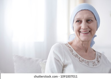 Upper body portrait of an older, female cancer patient looking happy and hopeful in a bright white interior