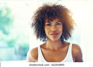 Upper body portrait of relaxed young black woman with frizzy hair in bright sunlight