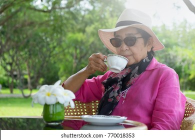 Upper body shot of an Asian elderly woman in bright pink blouse sitting in garden and sipping tea or coffee in a porcelain cup