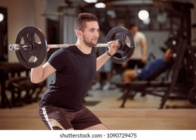 upper body shot, squat exercise, young man holding barbell with weights on back shoulders. Unrecognizable people behind in gym (out of focus)