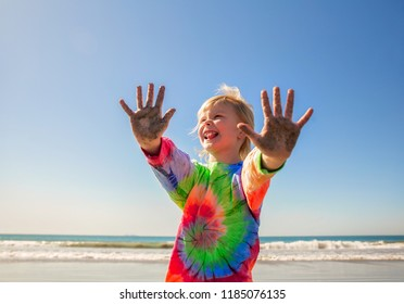 The upper body of a six year old girl in a tie dye shirt holding out sand covered hands and laughing eith a blurred ocean in the background on a sumer day