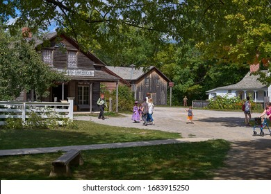 UPPER CANADA VILLAGE, MORRISBURG, ONTARIO, CANADA - October 17, 2019: tourists and visitors walk along the road in Ontario Open Air Heritage Museum.