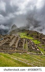 Upper complex of building in Machu Picchu with huayna picchu covered with clouds