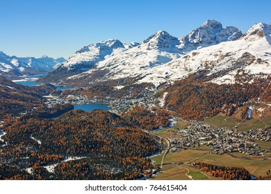 Upper Engadin Valley in the Swiss Alps. Autumn landscape with snow covered mountains, forests, lakes and the resort towns St. Moritz and Celerina in Grisons, Switzerland. With copy space.