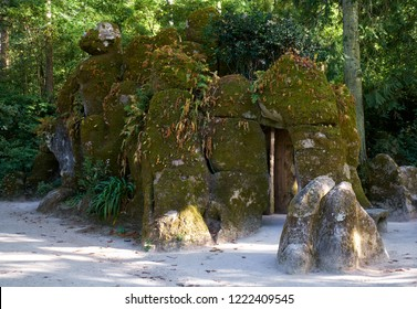 The upper entrance to the Initiation Well (Inverted tower) hided behind the mossy stones and vegetation in the park of Quinta da Regaleira estate. Sintra. Portugal