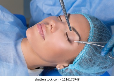 Upper eyelid blepharoplasty. Beautiful middle age woman getting ready for eyelid lift plastic surgery doctor hands in blue gloves point medical tools to her eye. Beauty, people and health concept