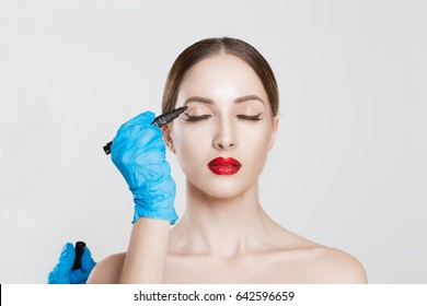 Upper eyelid reduction double eye lid removal plastic surgery cosmetic operation concept Woman eyes closed waiting doctor surgeon hand in gloves to draw cut line eyelid fat isolated white background