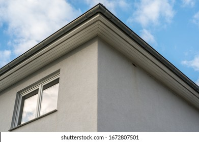 Upper floor of a white plastered house with roof box and double window