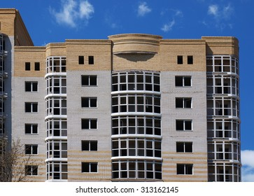 The upper floors of multistory building against the blue sky with clouds
