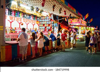 UPPER FREEHOLD, NEW JERSEY/USA -Â?Â? July 14: Teenagers at a carnival game at the Freedom Fest in Upper Freehold on July 14 2013 in New Jersey. The state fair is an annual event in Central New Jersey.