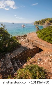 Upper half - idyllic turquoise blue beach, summer, sea, vacations season, but on down half - entrance in the bunker used to guard island Prvic, Croatia, female prison during communist era.Authentic.