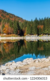 Upper Lake of Fusine, Tarvisio. Autumnal fire reflections. At the foot of the Mangart