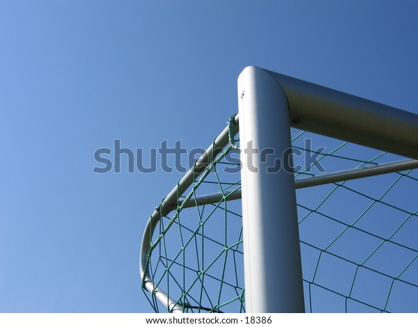 Upper left angle of an silver soccer goal with a green net.