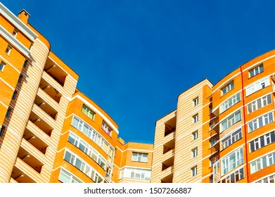 Upper part of the corner of an orange multi-story apartment building and blue sky.  View from below.