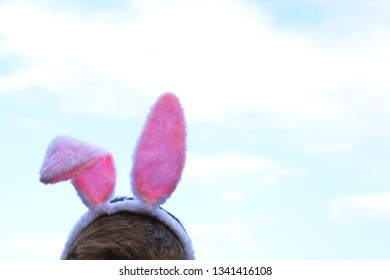 The upper part of a head freeze on the pink bunny ears are fastened against a slightly cloudy sky - concept with easter ears and place for text or other elements