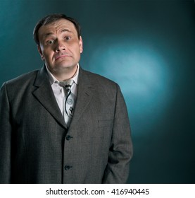Upper part of a man making funny face, dressed in jacket and tie standing against lighted background.