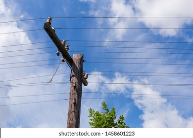 Upper part of the old wooden telegraph pole with utility spar, insulators and open telephone wires on a background of the sky