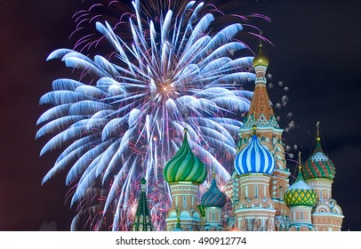 Upper part of  the Saint Basil's Cathedral at the Red Square in Moscow by a winter night with firework as a background. Roof is covered by snow.