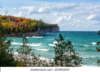 An Upper Peninsula forest creates an autumn background at Chapel Beach in northern Michigan. Lake Superior waves crash on the beach and white puffy clouds dot the blue sky.