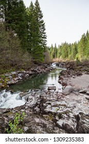 The Upper Rogue River beneath the Prospect Dam with fast moving clear water and volcanic rock embankments showing years of erosion.