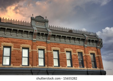 upper sandstone facade  of Miller Block (1888) at historic downtown of Fort Collins, Colorado against cloudy sky at sunset