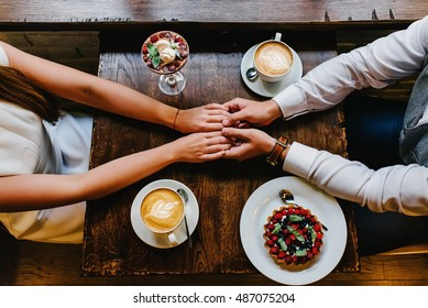 An upper sight of a couple at a cup of coffee in a cafe. couple in love holding hands in a cafe. Top view.