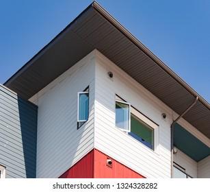 Upper storey detail of contemporary apartment condo building under blue sky