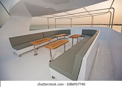 Upper sundeck of a large luxury motor yacht with chairs sofa table and tropical sea view background at sunset