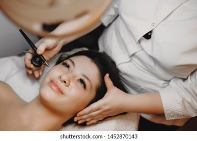 Upper view of a beautiful adult caucasian woman having oxygenation treatment on her face by a oxygenotherapy specialist.