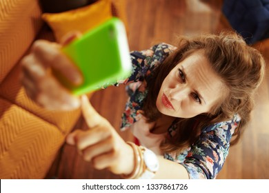 Upper view of concerned young housewife with long brunette hair at modern home trying to get better wifi signal on the smartphone.