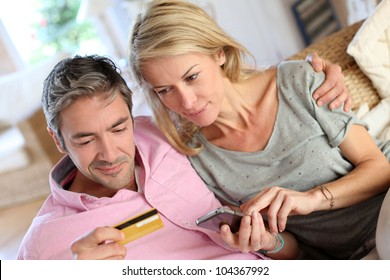 Upper view of couple paying with credit card on mobile phone