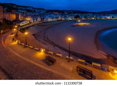 Upper view down on street with benches, street lights and handrail in front, ancient fortress battlement wall on rock, deserted beach and small marine town under cloudy sky in distance at dusk (Spain)