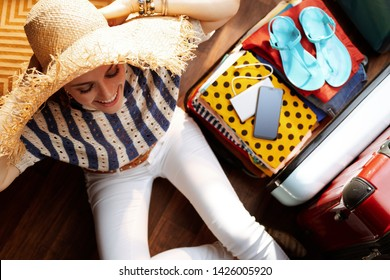 Upper view of happy stylish woman in white pants and striped blouse with big summer straw hat near open travel suitcase packing for summer vacation at modern home in sunny summer day.