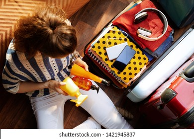 Upper view of modern woman in white pants and striped blouse in the modern house in sunny summer day packing summer cosmetics in open travel suitcase.